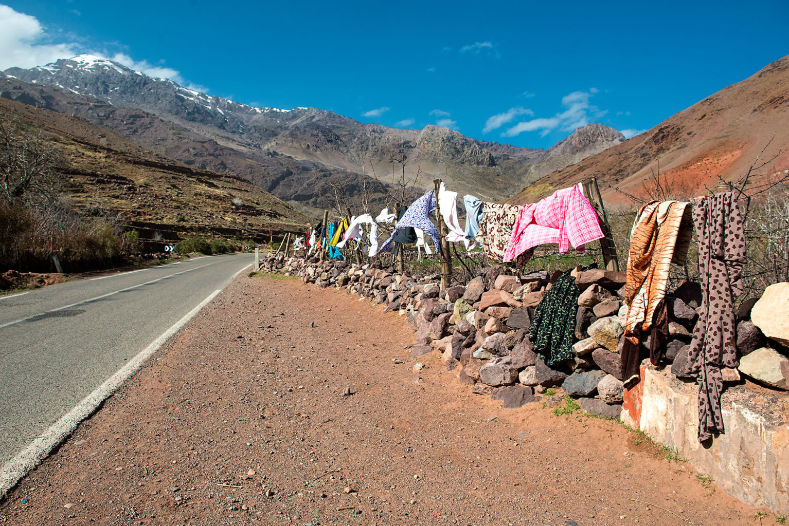 Berber Woman drying cloth along the road to the Atlas Mountains Morocco